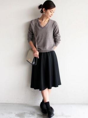 グレーのニットにミモレ丈スカートの女性