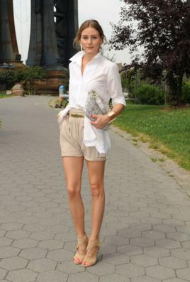 ベージュのショートパンツに白シャツを合わせる女性