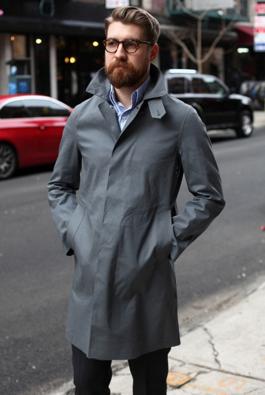 グレーのステンカラーコートを合わせる男性