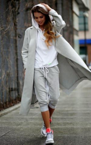 ロングコートにアスレジャーファッションの女性