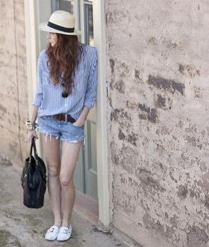 ブルーのピンストライプのシャツにデニムショーツをコーデした女性
