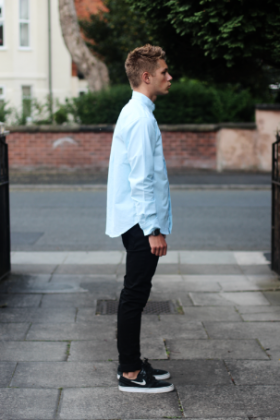 水色シャツにブラックパンツをコーデする男性