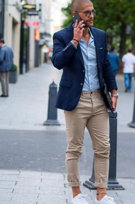 ネイビージャケットに水色シャツ、ベージュチノをコーデする男性