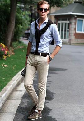 サックスブルーのシャツにベージュチノ、ニューバランスのスニーカーをコーデする男性