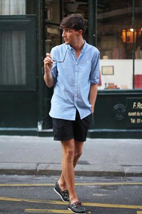 サックスブルーのオックスフォードシャツにショーツを合わせたコーデをする男性