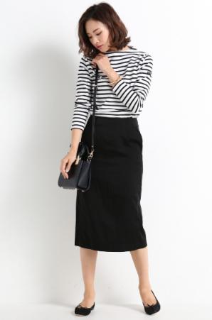 ミモレ丈スカートにペタンコ靴を合わせたコーディネートをする女性