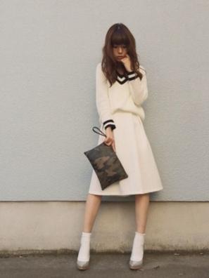白いチルデンニットに白いスカートをコーディネート、靴下も白でまとめたワントーンの女性