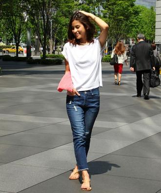 ホワイトTシャツにカットオフデニム、サンダルでコーデする女性