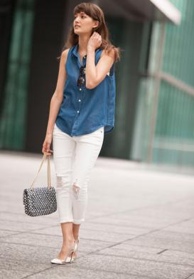ノースリーブデニムシャツにホワイトデニムパンツをコーデする女性