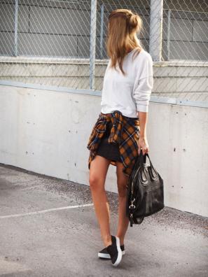 スウェットのトップスにミニスカート、チェックシャツを腰に巻く女性