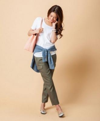 白の半そでカットソーにカーキのパンツをコーディネート、腰に巻いたデニムシャツがポイントの女性