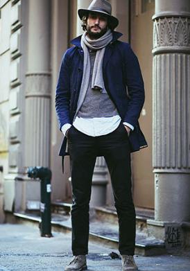 紺ジャケットにグレーニット、パンツはブラックでまとめた40代男性