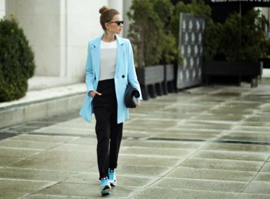 水色のチェスターコートに黒のジョガーパンツにアディダスのスニーカーを合わせる女性