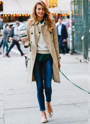 トレンチコートを着て犬を散歩させる外国人女性