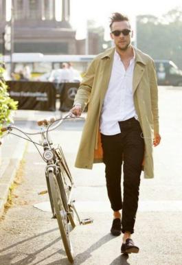 ベージュのトレンチを着た自転車を引く男