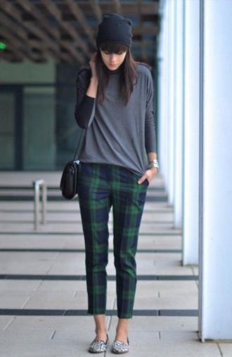 ブラックウォッチ柄のパンツを履く女性