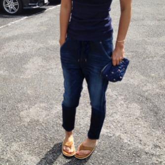 ヤヌークのデニムスウェットパンツにサンダルを合わせる女性