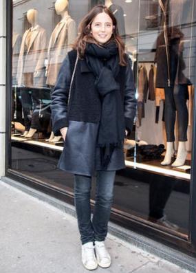 オールブラックな装いに白スニーカーの女性