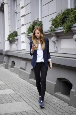 ネイビージャケット+ネイビースニーカーにブラックパンツを合わせる女性