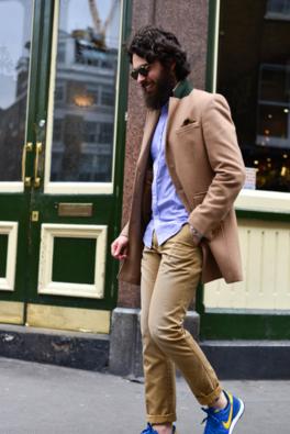 ブルーシャツにチェスターコート、ボトムはベージュパンツにブルースニーカーというおしゃれなコーデの男性