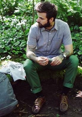 ギンガムチェックシャツにグリーンのチノパンを合わせる男性