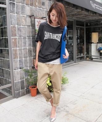 黒いロゴTシャツにベージュのパンツをコーデする女性