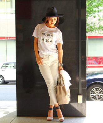 ホワイトのカットオフデニムにロゴ入り白Tシャツ、足元にはヒールでまとめた女性