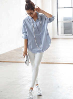 白いストレッチスキニーにブルーシャツ、スニーカーを合わせる女性