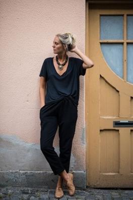黒のVネックTシャツに黒いスウェットをコーディネートする女性