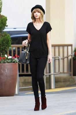 深めの黒いVネックTシャツにパンツも黒でワントーンコーデする女性