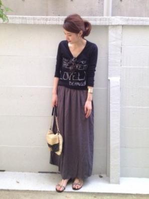 黒の深いVネックTシャツにプリーツスカートをコーデした女性