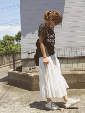 黒のロゴTシャツに白いロングスカートをコーデする女性