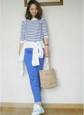 ボーダーTシャツにブルーのパンツを合わせる女性は腰にワンポイントの白シャツを巻いている