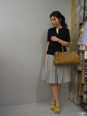 黒いポロシャツにストライプスカートをコーデする女性