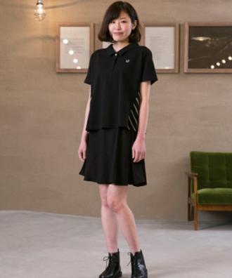 黒いポロシャツに黒スカートのワントーンコーデの女性