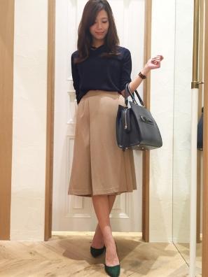 ネイビーシャツ×ベージュスカーチョのコーデをする女性