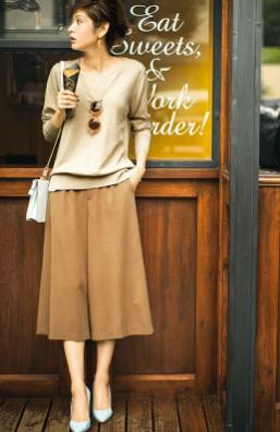 ベージュカラーのトップスにベージュのスカーチョを合わせるコーデをした女性
