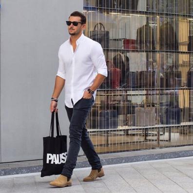 白シャツにグレーパンツを合わせて足元はブーツで決めた男性