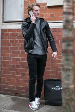 レザージャケットにグレーのタートルニット、ブラックパンツに白いナイキのスニーカーをコーデする男性