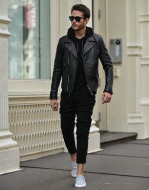 レザージャケットx黒パーカーxブラックパンツを合わせる男性