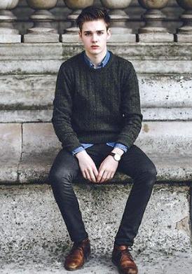 モスグリーンのニットにデニムシャツ、ブラックパンツをコーデする男性