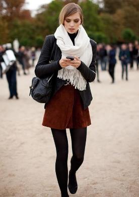 白のマフラーに黒レザージャケットを合わせる女性